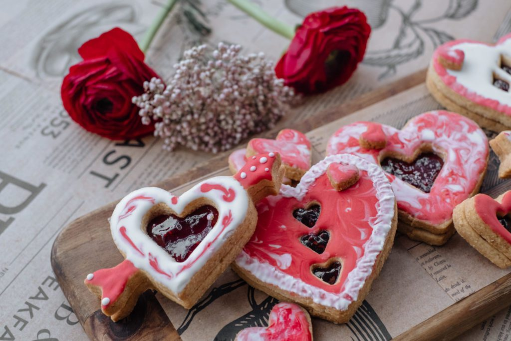 Board with variety of Valentine's red and white cookies and flowers.