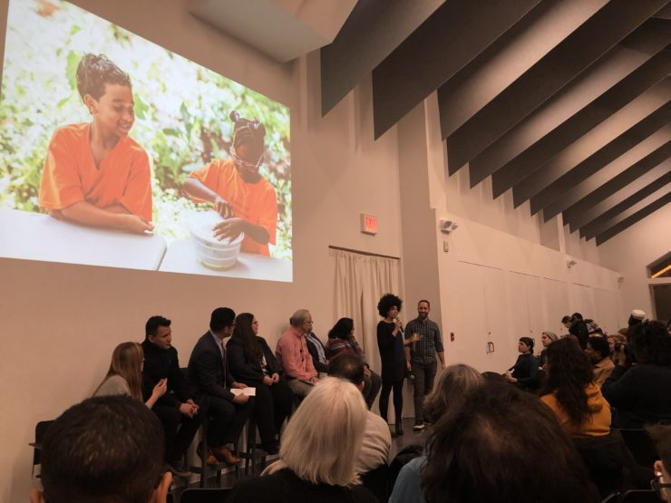 Panel at the conference with slide image of children on the wall.