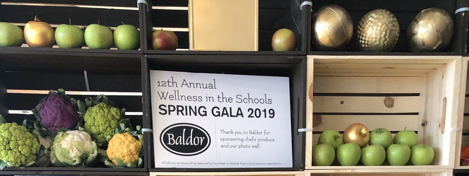 Wellness In The Schools Gala sign in wall with apples and cauliflowers.