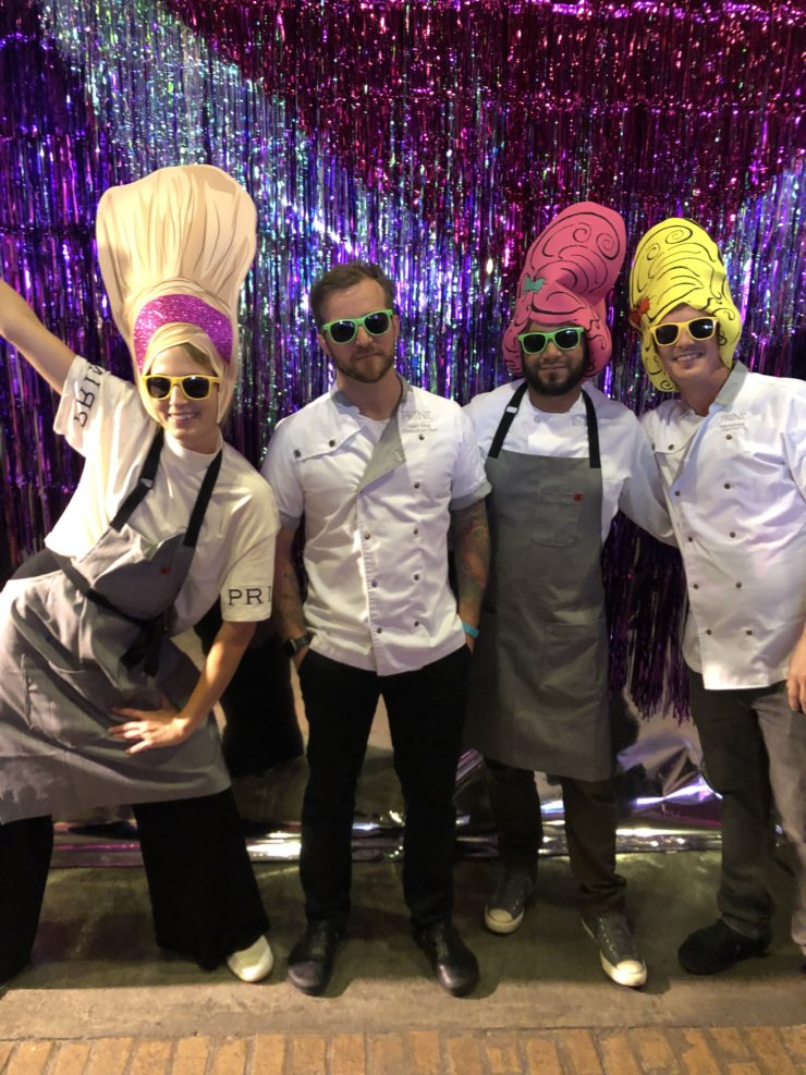 4 team members in sunglasses and whimsical hats for Drag Brunch.