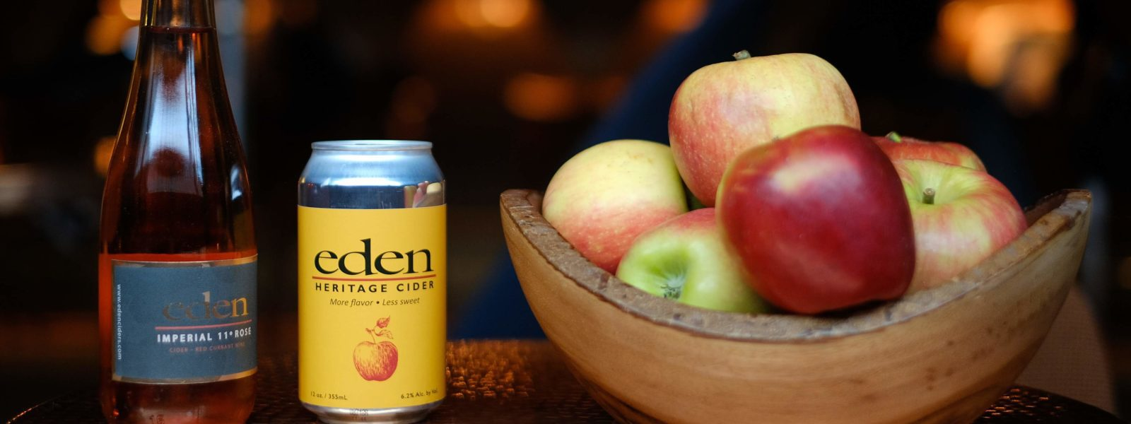 A bottle and can of cider with bowl of apples.