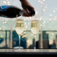Hand pouring champagne into 2 flutes with twinkle lights and city background.