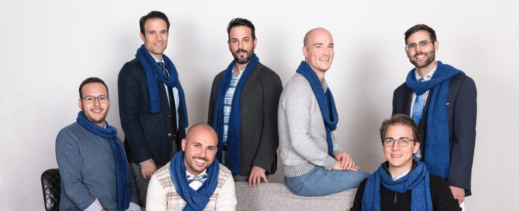 The 7 members of Men Singing Carols wearing blue scarves.
