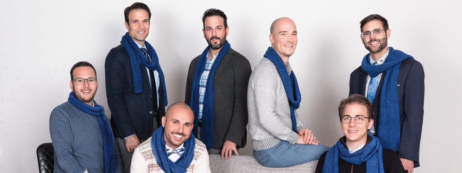 The 7 members of Men Singing Carols wearing blue scarves.