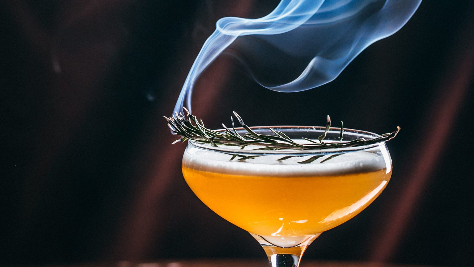 Cocktail in coupe glass with smoke rising from top.