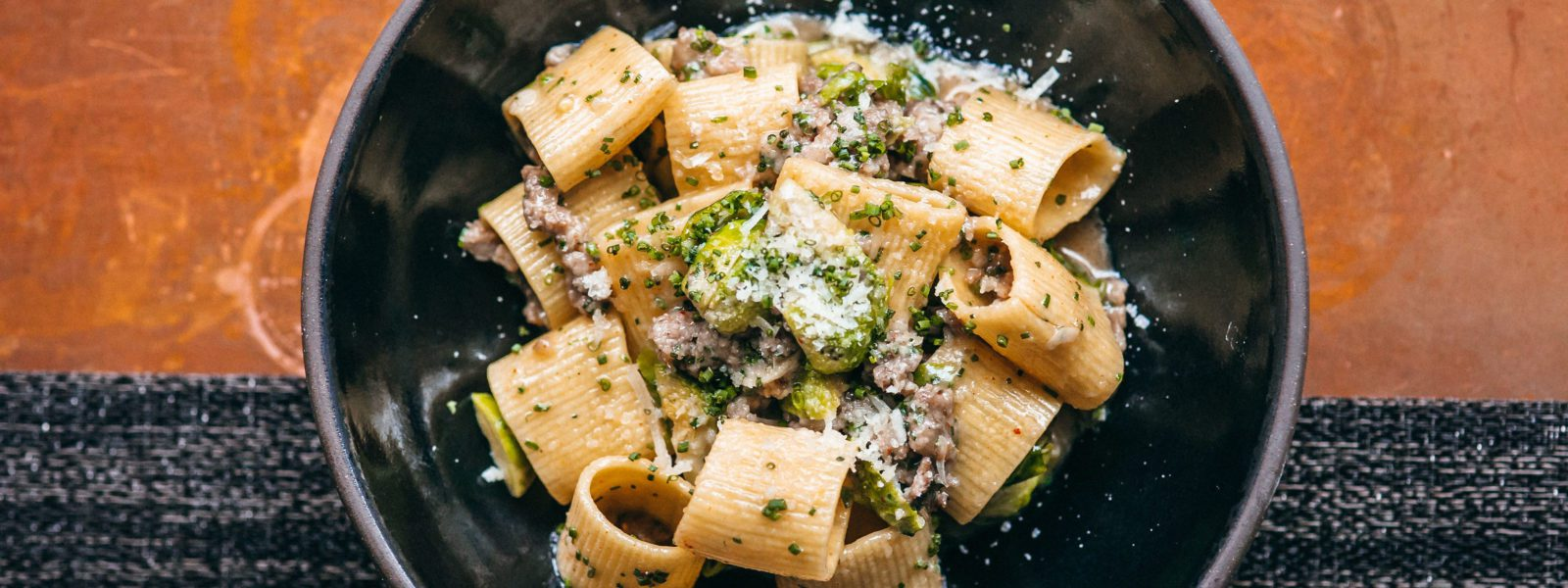 Rigatoni dish with fresh grated cheese and chives.